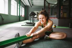 A beautiful girl with a smile stretches her muscles, kneads, warms up before training in a joint with a rubber band. Royalty Free Stock Image