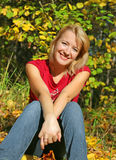 The beautiful girl smiles. In an autumn wood Royalty Free Stock Image