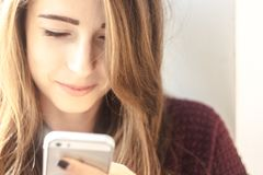 Beautiful girl smiles and looks into the phone Royalty Free Stock Image