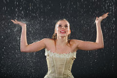Beautiful girl smiles in rain and catches drops Royalty Free Stock Photos