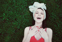 Beautiful young girl smiling laying on the grass Royalty Free Stock Photos