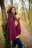 Beautiful girl smiling at the camera, in stylish autumn fashion clothes, in park scenery with trees and leaves. Gorgeous