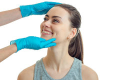 Beautiful girl smiling at doctor-cosmetologist with blue mittens  on a white background Royalty Free Stock Photography