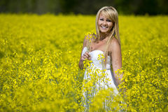 A beautiful girl smiling in a field of yellow flowers Royalty Free Stock Image