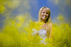 A beautiful girl smiling in a field of yellow flowers Stock Photo
