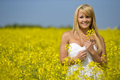 A beautiful girl smiling in a field of yellow flowers Stock Image