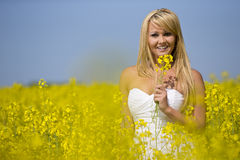 A beautiful girl smiling in a field of yellow flowers Royalty Free Stock Images