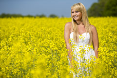 A beautiful girl smiling in a field of yellow flowers Stock Photography