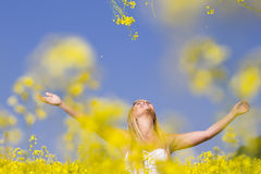 A beautiful girl smiling in a field of yellow flowers Royalty Free Stock Photos