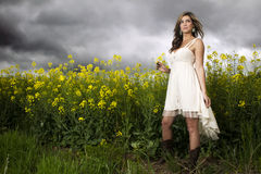 A beautiful girl smiling in a field of yellow flowers Royalty Free Stock Photography
