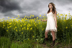 A beautiful girl smiling in a field of yellow flowers Royalty Free Stock Photo