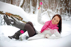 Beautiful girl smiling. Frost, winter. Beautiful brunette girl smiling, holding a pink flower. Winter, snow, frost Royalty Free Stock Photography