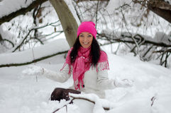 Beautiful girl smiling. Frost, winter. Beautiful brunette girl, holding a pink flower. Winter, snow, frost Royalty Free Stock Image