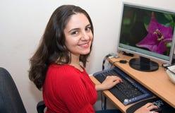 Beautiful girl smiling at her desktop Stock Photos
