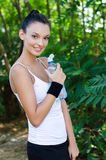 Beautiful girl smiling holding a bottle of water o Stock Image