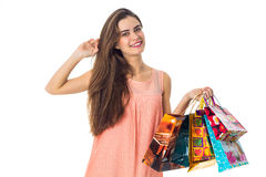 Beautiful girl smiling and holding in his hand a lot of packages from stores isolated on white background Royalty Free Stock Photography