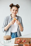 Beautiful girl smiling looking at camera holding grapefruit peace over white wall. Healthy fitness nutrition. Copy space Stock Images