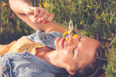 Beautiful girl smiling and lying on field and holding flower. S in her hand Stock Images