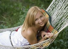 Beautiful girl smiling while lying in a hammock Royalty Free Stock Image