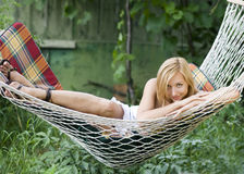 Beautiful girl smiling while lying in a hammock stock images