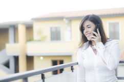 Beautiful girl smiling on the phone outdoor Stock Photos