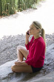 Beautiful girl smiling on phone sitting on stone in park Stock Photography