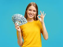 Beautiful girl smiling, shows money cash and excellent sign, demonstrates that everything is fine. Photo of girl in yellow sweater on blue background stock image