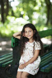 Beautiful girl smiling sitting on the bench in the park Stock Photos