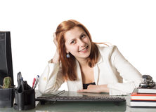 Beautiful girl smiling while sitting at a desk in an office Stock Image