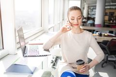 Beautiful girl is smiling. She is sitting near bright window in a beautiful sunny day and talking on the phone. She is stock photo