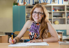Beautiful girl smiling while sitting at a table and writes Royalty Free Stock Image