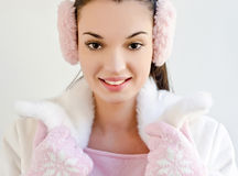 Beautiful girl smiling wearing pink ear muffs and cute gloves with snowflake. Royalty Free Stock Photography