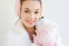 Beautiful girl smiling wearing pink ear muffs and cute gloves with snowflake. Stock Photography