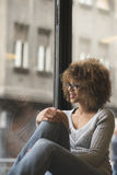 Beautiful girl smiling by the window at the coffee shop. Portrait of young mixed race girl sitting by the window Stock Photography