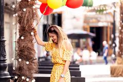 A blonde girl smiles with ballons in hand stock photo