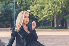 Beautiful girl smoking in the city streets Stock Image