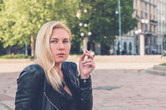 Beautiful girl smoking in the city streets Royalty Free Stock Photos