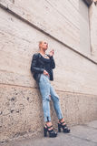 Beautiful girl smoking in the city streets. Beautiful blonde girl wearing ripped jeans and leather jacket smoking a cigarette in the city streets Stock Photography