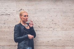 Beautiful girl smoking in the city streets Royalty Free Stock Photography