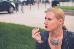 Beautiful girl smoking in the city streets Stock Photography