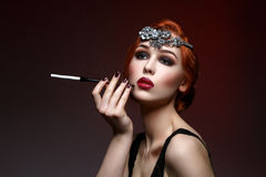 Beautiful girl with smoky eyes and red lips holding cigarette Stock Image