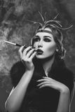 Beautiful girl with smoky eyes and red lips holding cigarette Royalty Free Stock Image