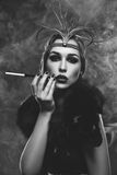Beautiful girl with smoky eyes and red lips holding cigarette. Beautiful young woman with smoky eyes and full red lips holding cigarette holder. Vintage head Stock Images