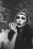 Beautiful girl with smoky eyes and red lips holding cigarette Stock Photo