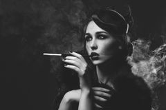 Beautiful girl with smoky eyes and red lips holding cigarette Stock Images