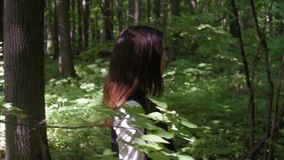 Beautiful girl sneaks through the trees in the forest stock video footage
