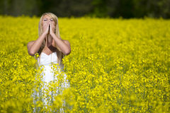 A beautiful girl sneezes in a field Royalty Free Stock Images