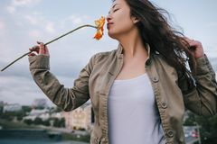 Beautiful girl sniffs scent of orange flower Royalty Free Stock Photo
