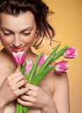 Beautiful girl sniffs a tulip. A studio portrait Stock Photography