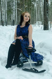 Beautiful girl on snow-scooter in winter forest Royalty Free Stock Photography